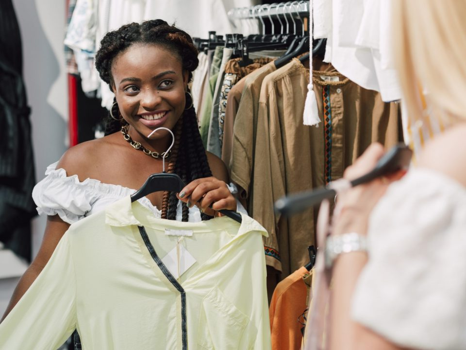vendedora mostrando roupas para cliente.